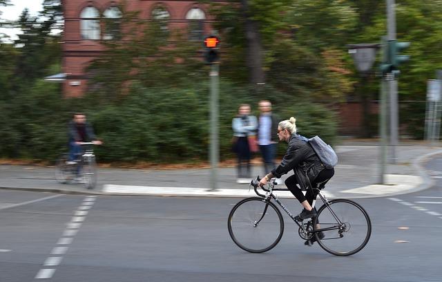 cyklistka projíždí městem