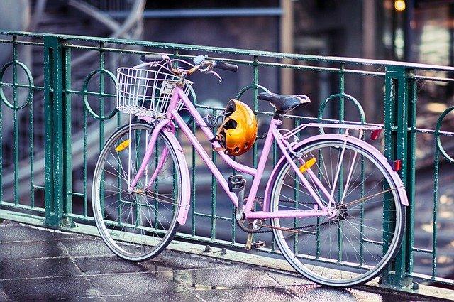 růžové dámské kolo a přilba