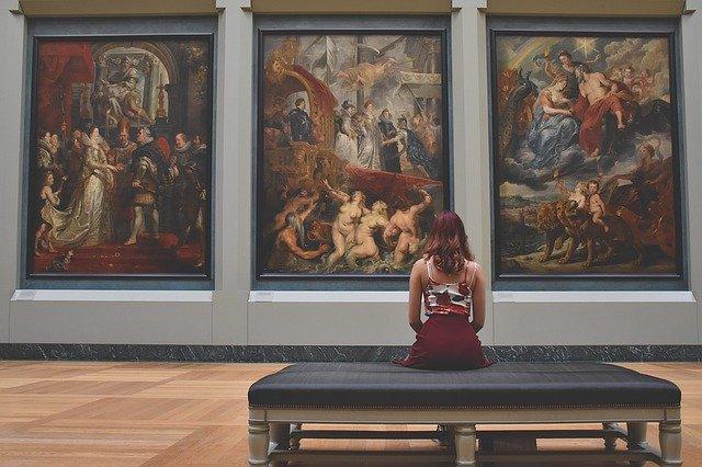 žena sedící před obrazy